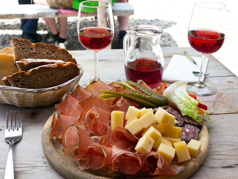 Tavolo di un'osmiza con affettati e vino